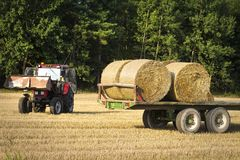 Agricultural machinery a tractor removes hay bales from the field after harvesting wheat. Harvest on the field. Harvesting of cereals. Agriculture royalty free stock images