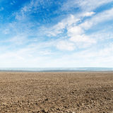 Agricultural plowed field and clouds in blue sky Stock Photo