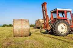 Agricultural scene. Tractor lifting hay bale on barrow. Agricultural scene. Tractor collecting hay bales in field and loading on farm wagon Royalty Free Stock Photos