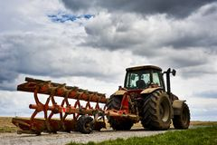 Agricultural scenery. A red tractor parked in a field under dramatic sky. Ideal for describing any agricultural scenery Royalty Free Stock Photo