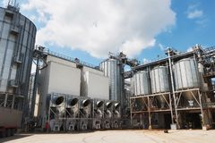 Agricultural Silos. Building Exterior. Storage and drying of grains, wheat, corn, soy, sunflower against the blue sky Royalty Free Stock Images