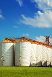 Agricultural silos under blue sky, in the fields Royalty Free Stock Photo