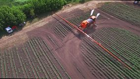 Agricultural sprayer moving on farming field and making watering plant stock video