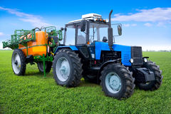 Agricultural spraying machine. Closeup of tractor attached to agricultural crop spraying machine on field in countryside Royalty Free Stock Image