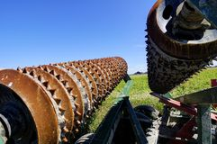 Agricultural tillage machinery placed by the farm field Stock Photography