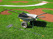 Agricultural tools. Garden trolley, fan rake and shovel  on green lawn Royalty Free Stock Image