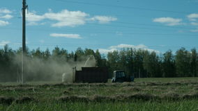 Agricultural tractor collecting a straw in the field stock video footage