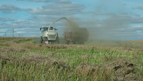 Agricultural tractor collecting a straw in the field stock footage