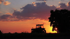 Agricultural Tractor on Cultivated Field Returning Home in Sunset stock video