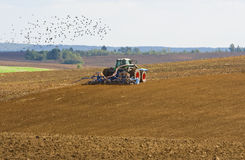 Agricultural tractor cultivating on farmland. In autumn Royalty Free Stock Photo