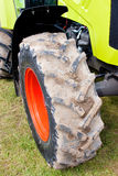 Agricultural Tractor Detail of Red Wheel. Agricultural Four Wheel Drive Tractor Detail of Red Wheel with Vibrant Green Body Stock Photo