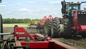 Agricultural tractor driving on arable field for plowing land. Farming industry stock video footage