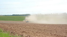 An agricultural tractor plowing a field. Hills and a forest at the background. Soil dust all over stock video