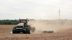 An agricultural tractor, plowing a field, moving to the camera. A forest in the background. stock footage