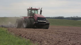 An agricultural tractor plowing a field, moving to the camera. stock video