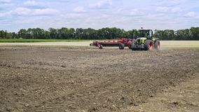 Agricultural tractor plowing field. Process plowing arable field. Plowed land stock footage