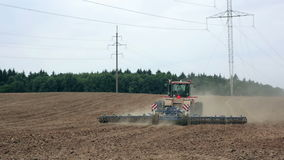 An agricultural tractor, plowing a field before sowing, moving from the camera. A forest in the background. stock video footage