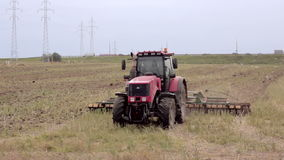 An agricultural tractor, plowing a field for sowing, moving to the camera. Birds are flying around stock video