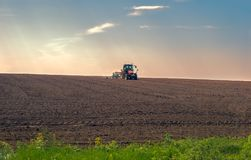Agricultural tractor plows the land. Panoramic view Stock Photography