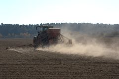 Agricultural tractor pulling a planter behind it, over a field and throwing up lots of dust. Agricultural tractor pulling a planter, also known as a seed drill royalty free stock photo