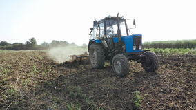 Agricultural tractor sowing and cultivating field at organic eco farm. Real working process at small family farm Royalty Free Stock Photography