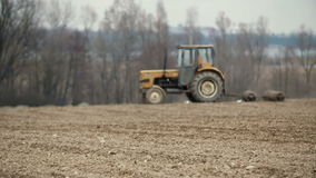 Agricultural tractor sowing and cultivating field stock video