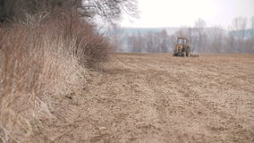 Agricultural tractor sowing and cultivating field stock video footage