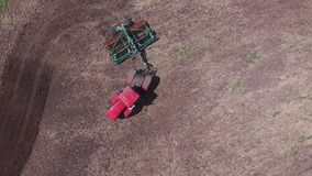 Agricultural tractor sowing seeds and cultivating field stock video footage