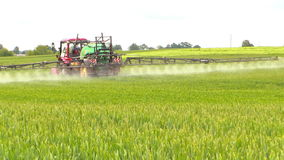 Agricultural tractor spraying fertilizer on farm fields stock video