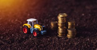 Agricultural tractor toy and golden coins on fertile soil land. Income from activity in agriculture or investment and bank loans for farm development Royalty Free Stock Photography