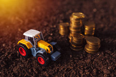Agricultural tractor toy and golden coins on fertile soil land. Income from activity in agriculture or investment and bank loans for farm development Royalty Free Stock Photos