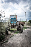 Agricultural tractor trailer at the road in the evening against a cloudy sky. Tractor with a trailer at the road in the evening against a cloudy sky Stock Photo