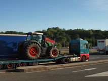 AGRICULTURAL TRACTOR TRANSPORTED BY TRUCK royalty free stock image
