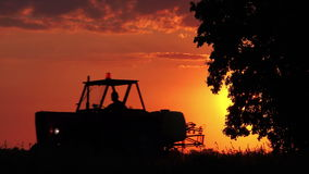 Agricultural Tractor with Unrecognizable Farmer Silhouette on Cultivated Field stock footage