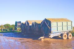 Agricultural trailers. Used to store animal feed with irrigation pipe on reel Royalty Free Stock Photo