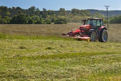 Agricultural work. Red tractor mowing the meadow, Czech Republic. Farmer harvested hay. Royalty Free Stock Images