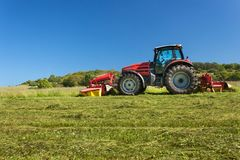 Agricultural work. Red tractor mowing the meadow, Czech Republic. Farmer harvested hay. Royalty Free Stock Image