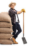 Agricultural worker leaning on pile of burlap sacks Stock Images