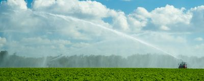 Trucks irrigating green field Royalty Free Stock Photography