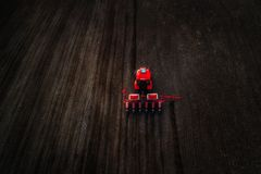 Aerial view of red tractor preparing field Stock Photos