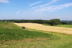 Agriculture, agronomy and farming background. Rural landscape with blue sky over farmers fields and meadows. Beautiful summer countryside nature background royalty free stock photo