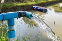 Agriculture blue pipe with groundwater gushing. In pond stock images