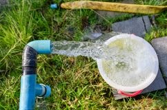 Agriculture blue pipe with groundwater gushing in plantation. Agriculture blue pipe with groundwater gushing in bucket at plantation stock images
