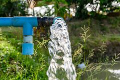 Agriculture blue pipe with groundwater gushing. S stock images