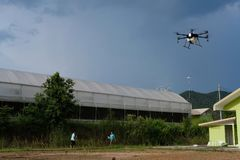 Agriculture drone flying & spraying liquid fertilizer or herbici. Chiang Mai, Thailand - September 7, 2018: man flying agriculture drone for spraying liquid Stock Photo