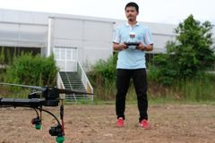 Agriculture drone for spraying liquid fertilizer or herbicide in. Chiang Mai, Thailand - September 7, 2018: man controlling agriculture drone for spraying liquid Stock Images
