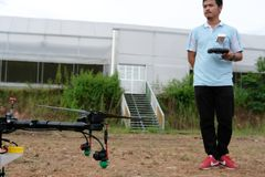 Agriculture drone for spraying liquid fertilizer or herbicide in. Chiang Mai, Thailand - September 7, 2018: man controlling agriculture drone for spraying liquid Royalty Free Stock Photos
