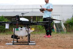 Agriculture drone for spraying liquid fertilizer or herbicide in. Chiang Mai, Thailand - September 7, 2018: man controlling agriculture drone for spraying liquid Royalty Free Stock Photography