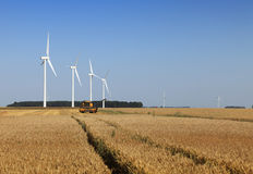 Agriculture and energy. Image of wind turbines and a combine in a wheat field Royalty Free Stock Photography