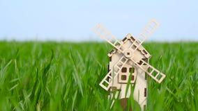 Agriculture et agriculture Un petit moulin décoratif fait de supports en bois parmi l'herbe verte d'un champ de blé Le concept banque de vidéos